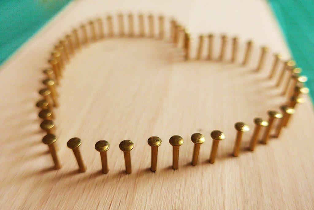 Złote gwoździe wbiłam w deskę do krojenia tak, aby powstało z nich serce.