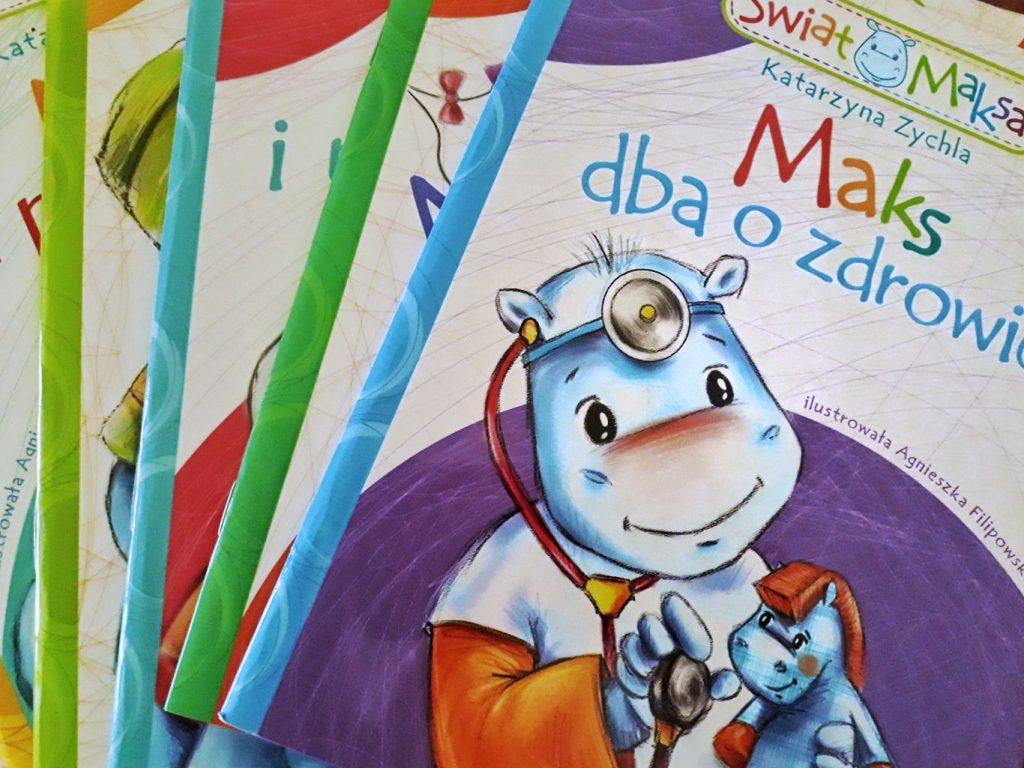"""Książeczki z serii """"Świat Maksa"""" sa niezwykle barwne i kolorowe, a przy tym są krótkie. Tutaj okładka książki """"Maks dba o zdrowie"""", gdzie hipopotamek na założony stetoskop i bada zabawki."""