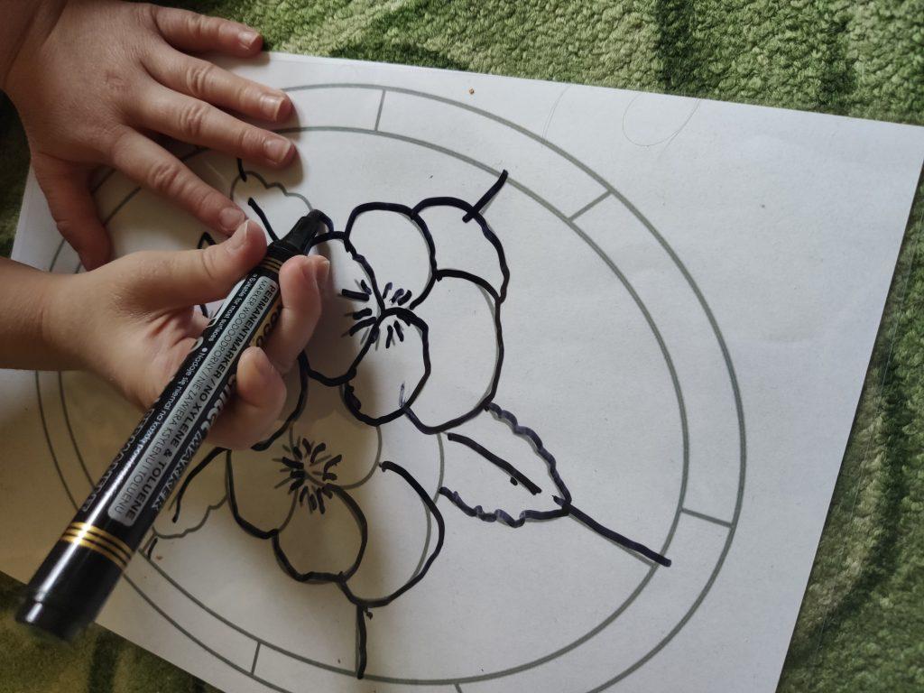 Dziecko poprawia kontur kolorowanki markerem