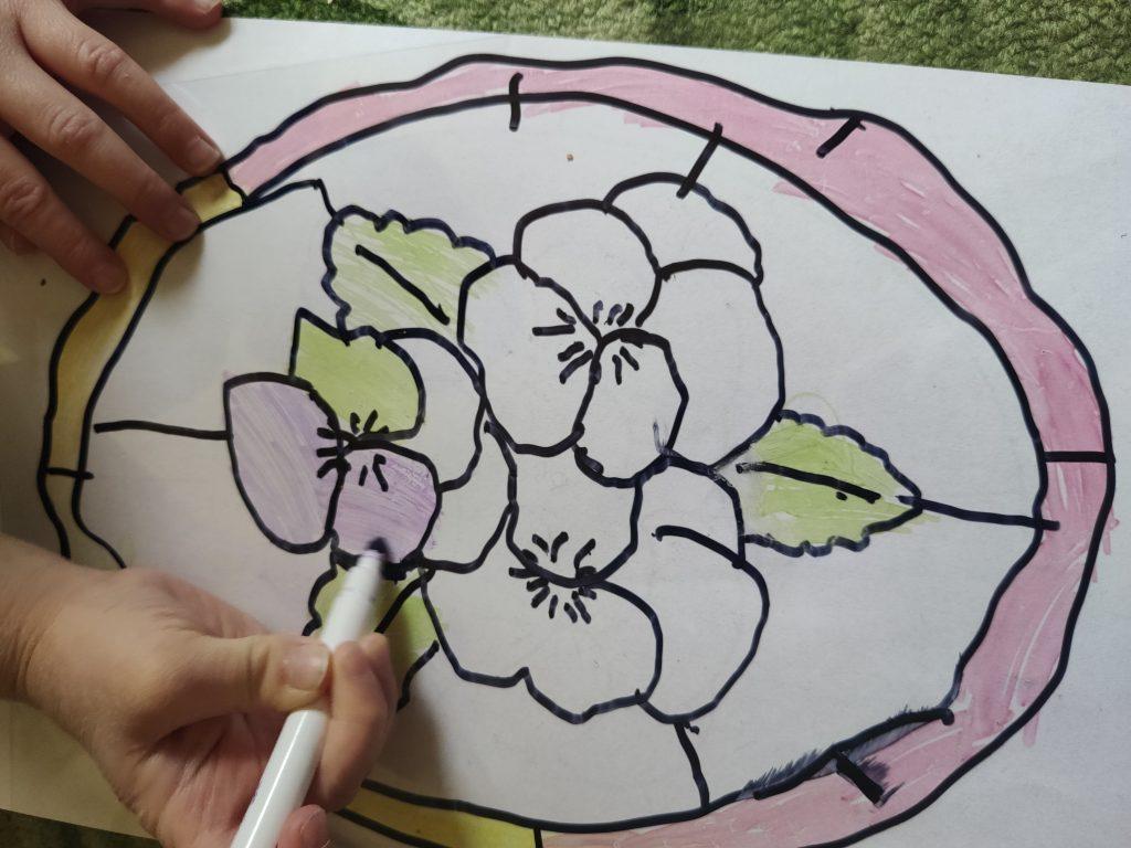 Dziecko koloruje rysunek mazakami na folii